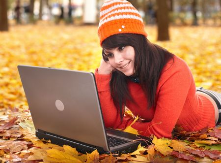 Young woman in autumn orange leaves with laptop. Fall sale. Outdoor. photo