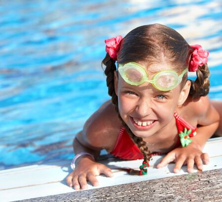 Little girl with protective goggles and red swimsuit in swimming pool. photo