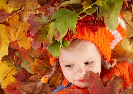 Girl child in autumn orange leaves. Outdoor. photo