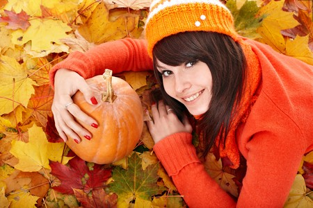 Happy young woman with  pumpkin on autumn leaves. Outdoor. Stock Photo - 7890099