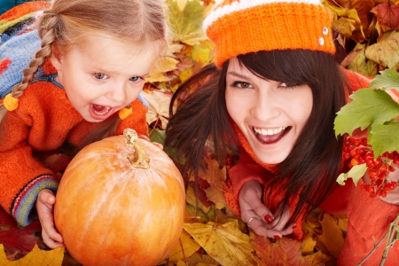 Happy family with  pumpkin on autumn leaves. Outdoor. photo