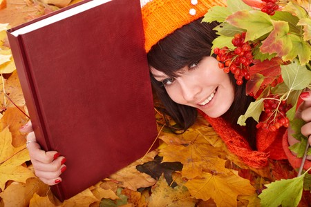 Girl in autumn orange leaves with book.  Outdoor. photo