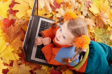 Little girl in autumn orange leaves with laptop. Outdoor. Stock Photo - 7890077