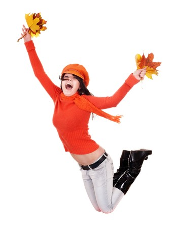 Girl in autumn orange sweater with leaves jumping. Isolated. photo