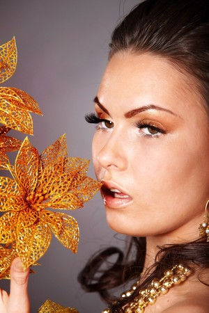 Beautiful young woman with gold flower on grey background. photo
