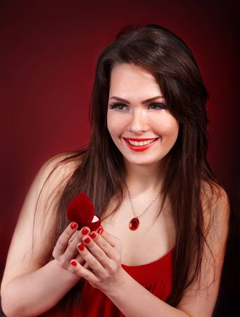 Girl with jewellery box on red background. Valentines day. photo