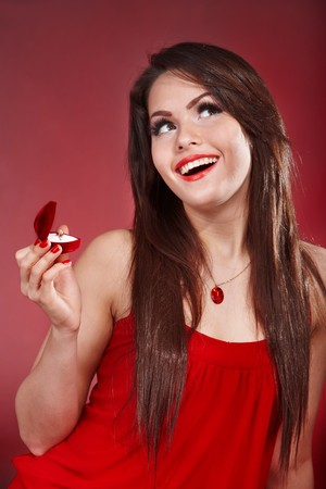 Young woman with jewellery gift box on red background. Valentines day. Stock Photo - 7889990