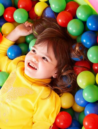 Happy little girl in group colourful ball. photo