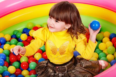 Happy little girl in group colourful ball. Stock Photo - 7890078