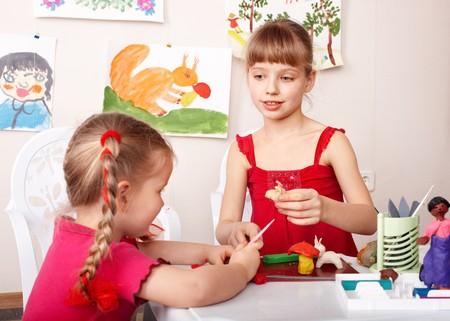 playroom: Los ni�os moldean plastilina en la sala de juego.