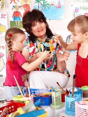 Teacher learn children painting picture  in preschool. photo
