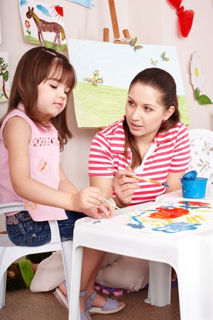 Little girl playing with teacher in preschool. photo