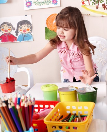 age care: Little girl paint picture in preschool. Stock Photo