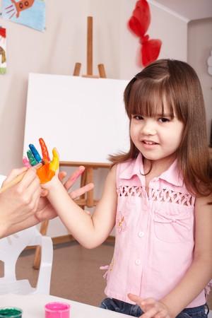 Little girl  making hand prints. Stock Photo - 7890054