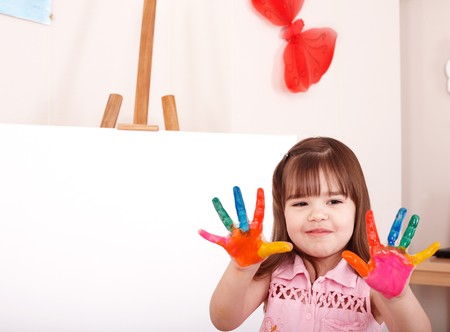 Little girl  making hand prints. photo