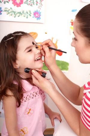 painting face: Ni�os en edad preescolar del ni�o con la pintura de la cara. Cuidado de ni�os.  Foto de archivo
