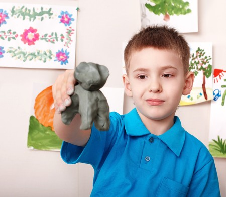 Little boy playing with clay. photo