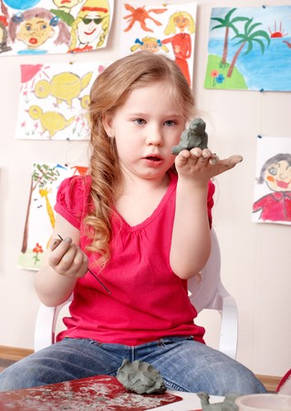 Little girl playing with clay. photo