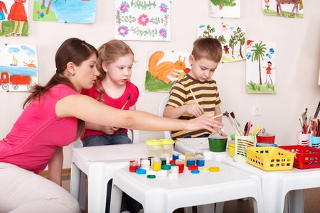 Children painting with teacher in art class. Child care. Stock Photo - 7889912