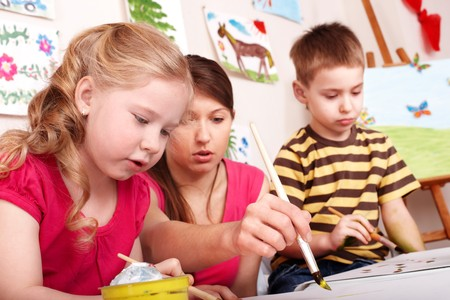 Children painting with teacher in play room. Stock Photo - 7890016
