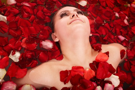 Beautiful girl in jacuzzi with rose petal. Body care. photo