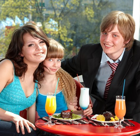 Happy family with child in restaurant. Parenting. photo
