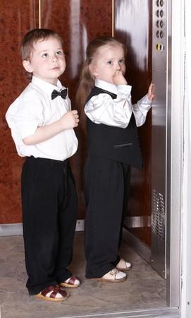 ascensor: Children in business suit take  elevator. Concept.
