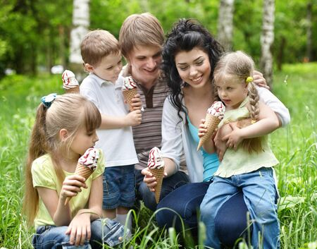 upbringing: Family with kids eating ice-cream. Outdoor. Stock Photo