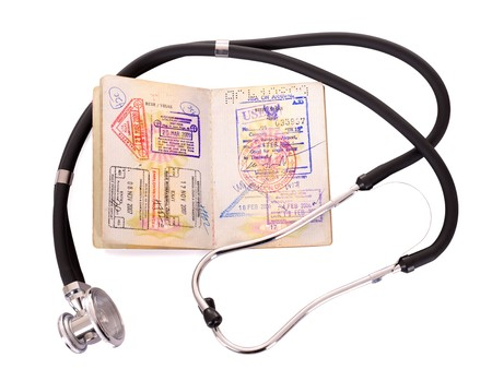 overseas visa: Medical still life with stethoscope and passport. Isolated.
