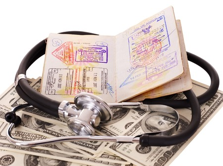 Medical still life with stethoscope, money and passport. Isolated. Stock Photo - 7890163