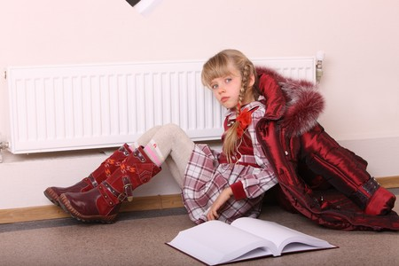 Girl lie near radiator with book. Cold crisis. Stock Photo - 7890149