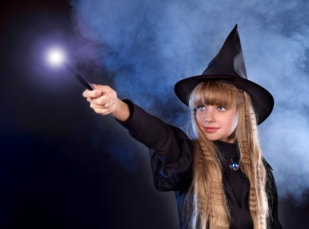 Girl in witch's hat with magic wand casting spells. Stock Photo - 7890133