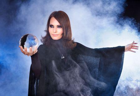 bruja: Mujer joven y hermosa con la bola de cristal.