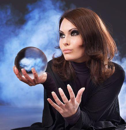 Hermosa joven con la bola de cristal.  Foto de archivo
