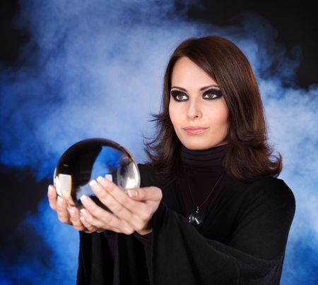 clairvoyant: Young beautiful woman with crystal ball. Stock Photo