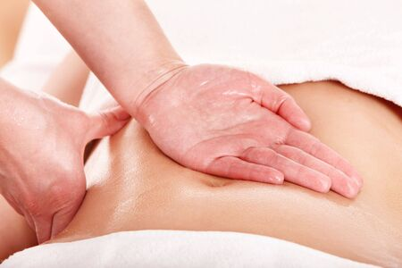 parlor: Beautiful young woman having stomach massage. Stock Photo
