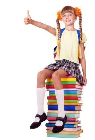 školačka: Girl sitting on pile of books showing thumb up. Isolated.