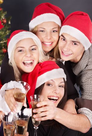 Group young people in santa hat drinking champagne at nightclub. photo