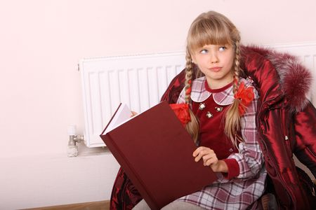 Girl lie near radiator with book. Cold crisis. Stock Photo - 8116504