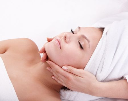 Beautiful young woman in spa. Facial massage. photo