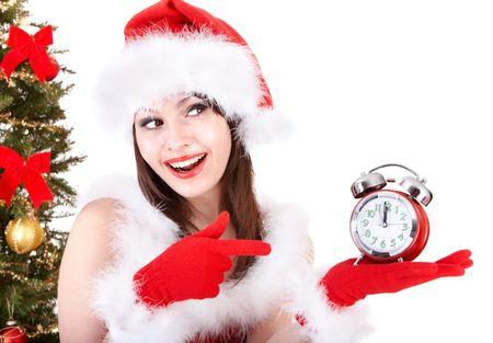 Girl in santa hat point on alarm clock near christmas tree.  Isolated. Stock Photo - 8239257