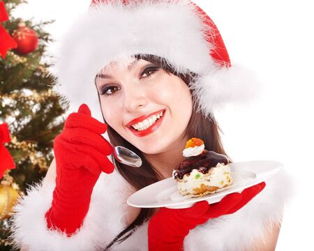 holiday meal: Christmas girl in red santa hat eating cake on plate. Isolated.