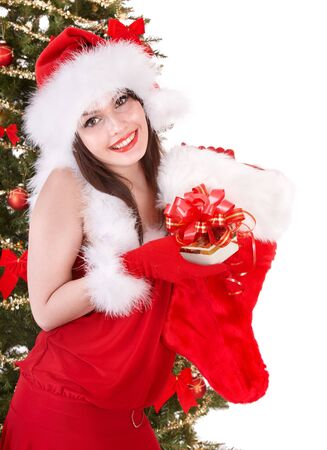 Girl in santa hat holding christmas socks and gift box near christmas tree.  Isolated. Stock Photo - 8239276