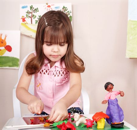 plasticine: Little girl playing with plasticine in school. Stock Photo