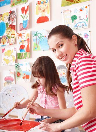 Little girl painting with teacher in preschool.  photo