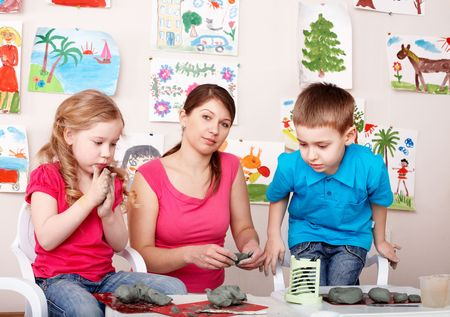 Children playing  with teacher from clay. Child development. photo