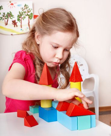 Little girl preschooler play wood block in play room. photo