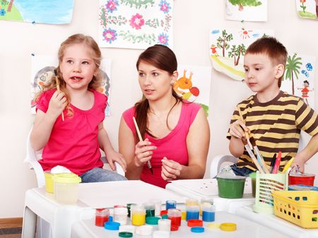 Child with teacher draw paints in play room. Preschool. Stock Photo - 8239252