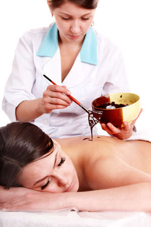 Girl having chocolate body mask apply by beautician. Isolated. photo