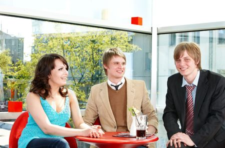 Group of happy young people talking in cafe. photo